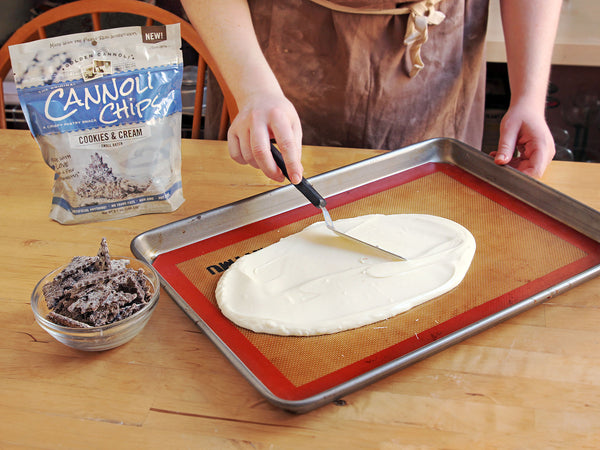 Spreading white chocolate for cookies and cream cannoli chip bark