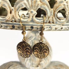 "Load image into Gallery viewer, These brass ox earrings are a wonderful gift for Fleur de Lis lovers. The round brass ox convex medallions are embossed with the fleur de lis design.  The medallions are attached to oxidized brass French wire earrings. Each pair of earrings comes on a display/gift card. The dimensions are 1.25"" round."