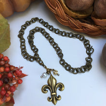 "Load image into Gallery viewer, Our double link antique brass chain holds a stunning  antique gold fleur de lis embellished with crystal beads.   The necklace is 18"" long and the closure is a toggle clasp.   This comes in a suede pouch for easy gift giving.  Sure to please fleur de lis lovers!"