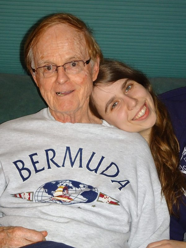 woman smiling with grandfather who has parkinson's