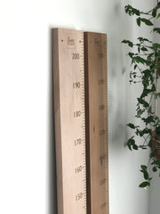 Whitewashed and natural rimu height chart rulers side by side