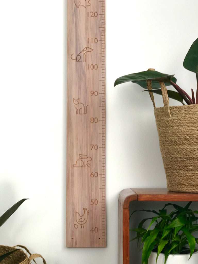 Bottom of modern animals carved into recycled rimu height chart
