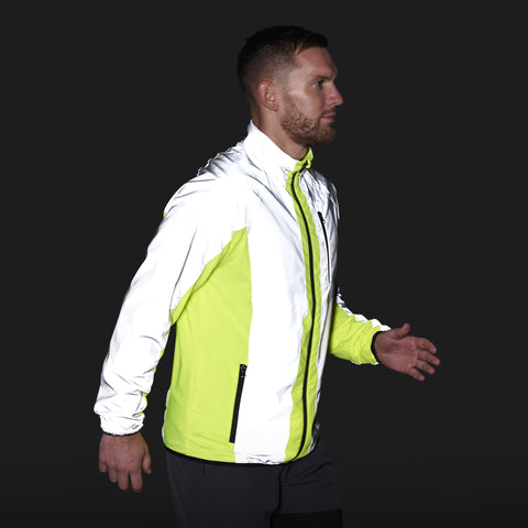BTR sports jacket shown on the side view in the dark - reflective panels shining bright