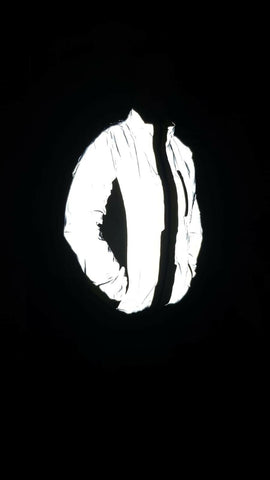 Be Totally Reflective jacket shown worn by a customer in the dark with flash