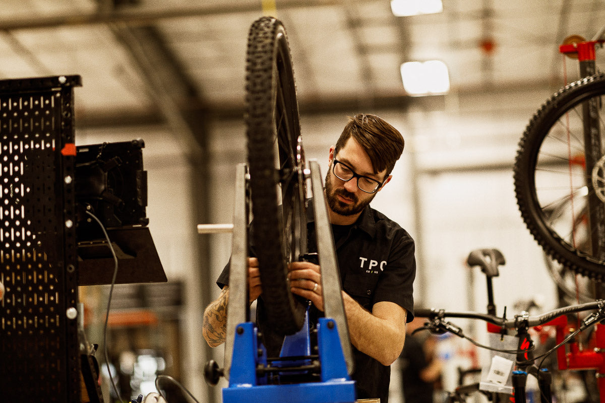 Bike technician truing a used bike wheel