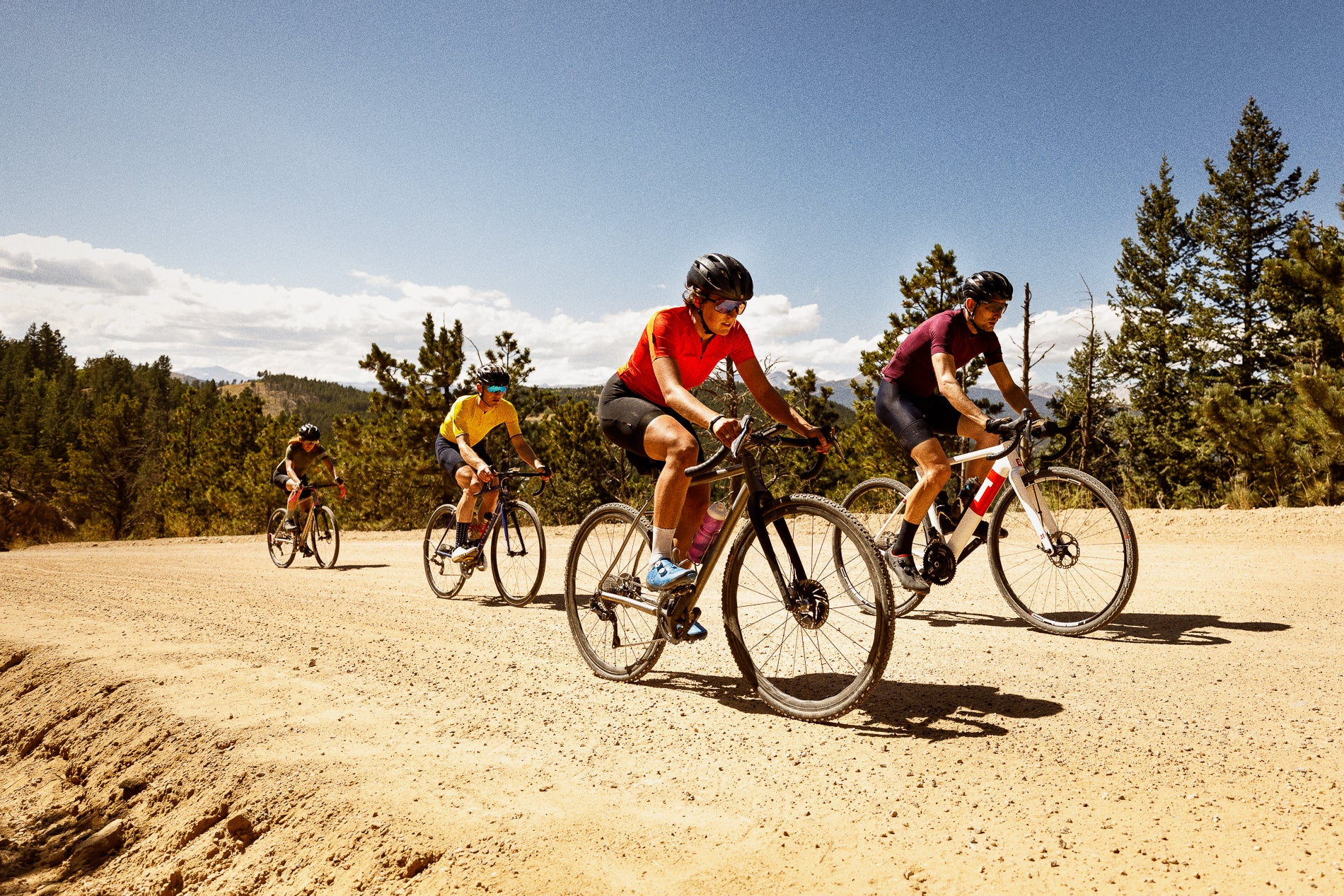 A group of people riding bikes on gravel roads
