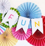 Bright letter banner, with the word Fun. It's hanging over colourful paper fans. Party decor items