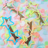 Star glasses on a table of neon confetti