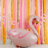 Flamingo Balloon in front of a streamer back drop