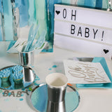 Oh Baby sign on table of party essentials in silver and blues