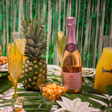 Pineapples plates, champagne flutes and gold forks