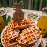 A stack of delicious waffles with a glittery gold pineapple topper