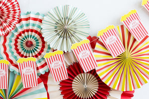 Popcorn banner, in traditional red stripes. Hanging on the wall against paper party fans.
