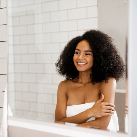 women-with-curly-hair-standing-in-front-of-mirror