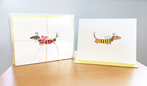 Dachshund assorted note cards with stationery box tied with yellow ribbon, examples are black and tan dachshund dressed as ladybug and brown dachshund dressed as bee