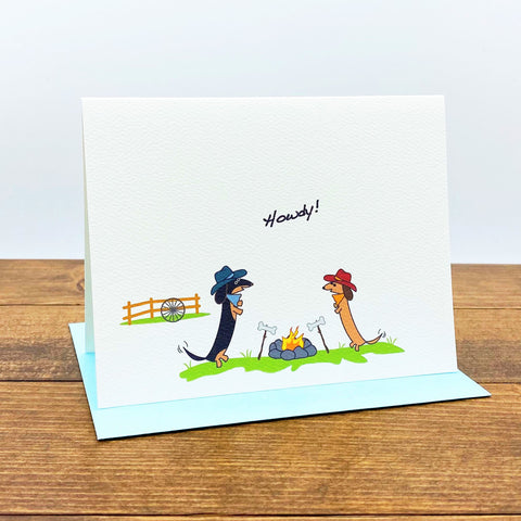 "Two dachshunds wearing cowboy hats enjoying a bonfire on ranch.  The card message is ""Howdy!"""