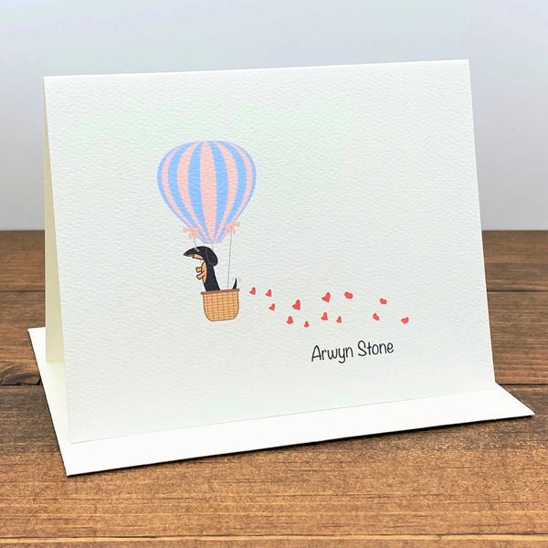 Personalized note card with black and tan dachshund in hot air balloon with trail of hearts behind it.