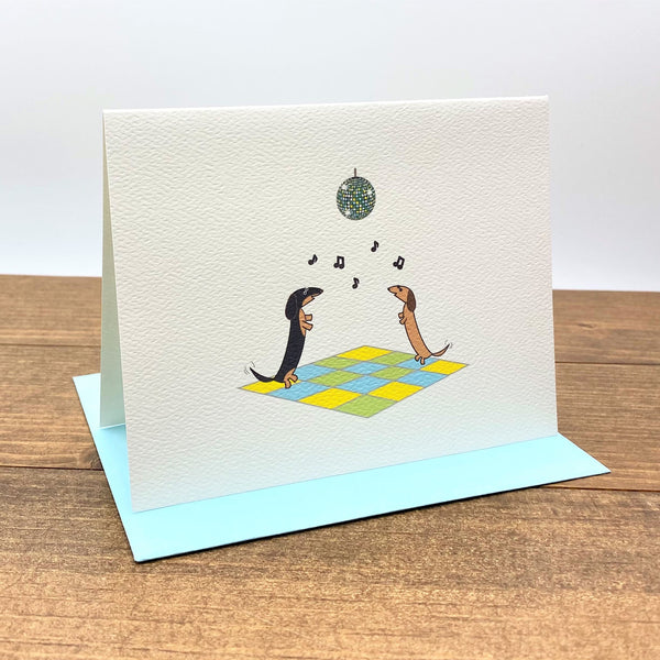 Two dachshunds dancing under disco ball note cards