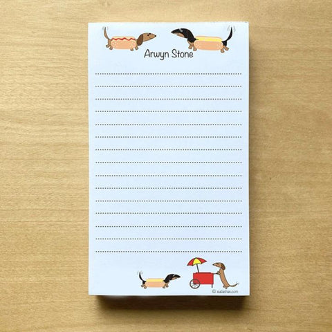 Two dachshunds dressed as hot dogs facing each other with personalized text below them and a hot dog cart  in the bottom corner of this lined notepad