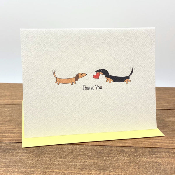 On the folded note card there are two dachshunds facing each other, one is brown and the other one is black and tan and holding a heart in its mouth.  The card  message is Thank You.