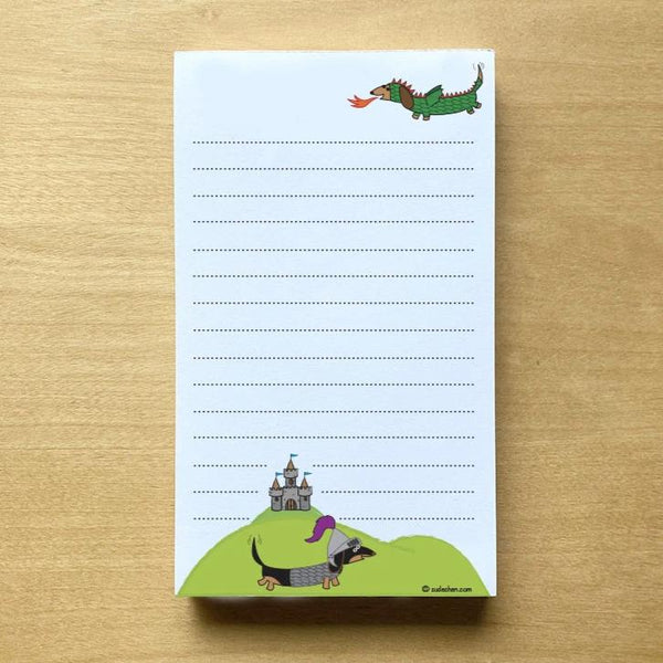 One dachshund dressed as dragon and the other as a knight with medieval castle in background in this lined notepad