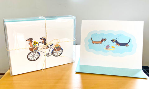 Traveling dachshunds assorted card set in clear stationery box tied with yellow twine, two card examples are two dachshund riding a bicycle and two dachshunds snorkeling under the sea