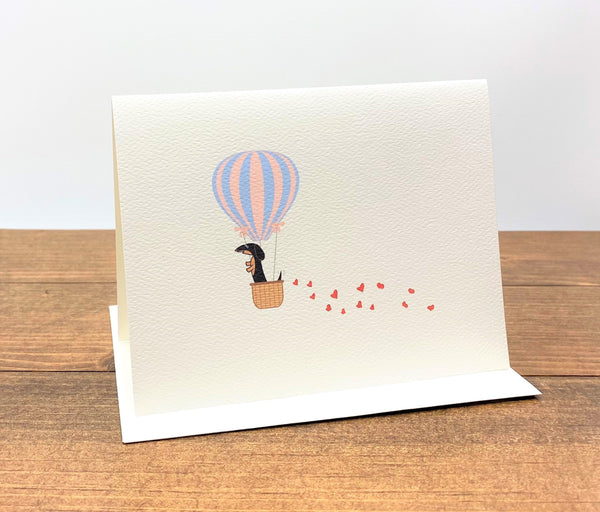 Note card with black and tan dachshund in hot air balloon with trail of hearts behind it.