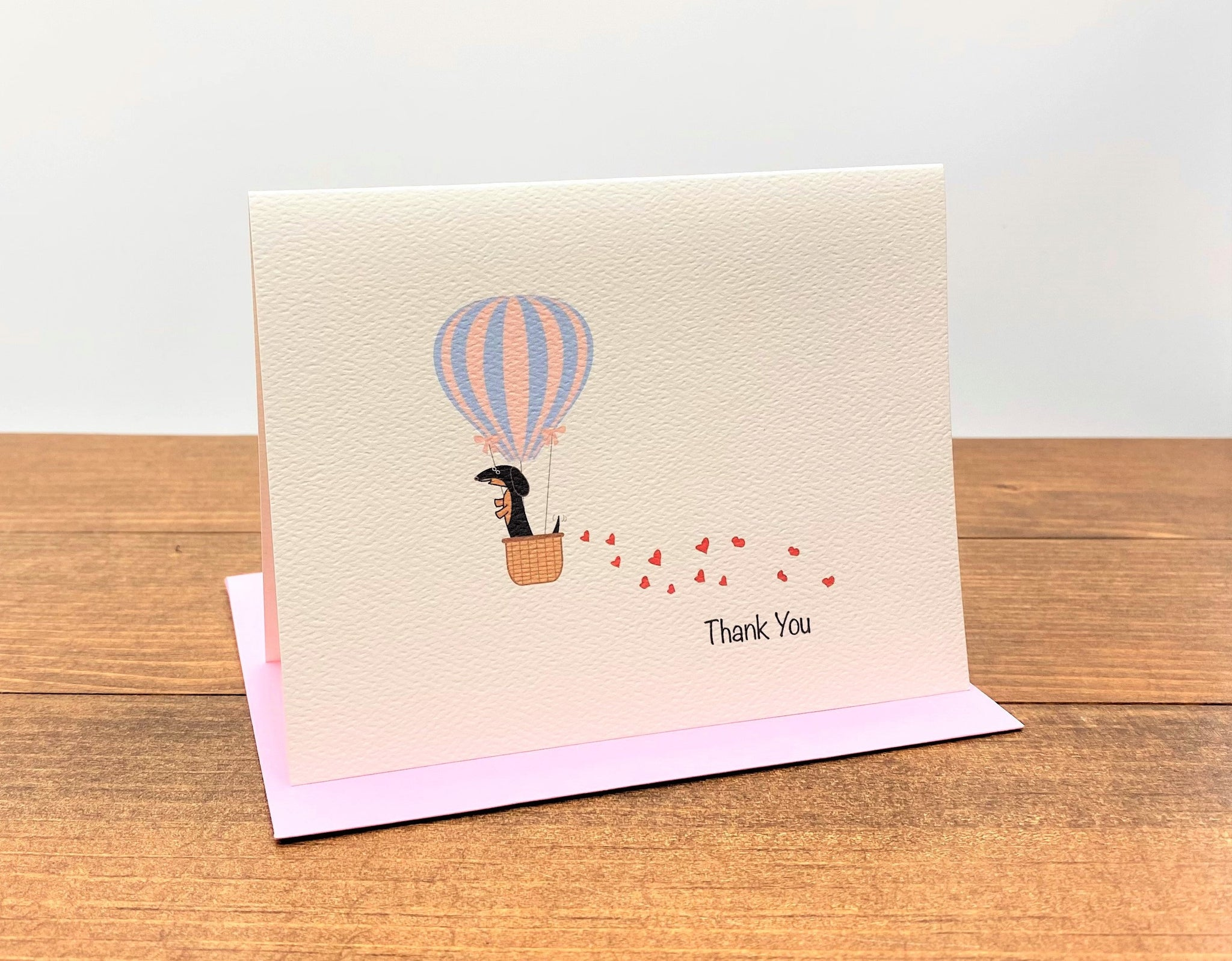 Thank you note card with black and tan dachshund in hot air balloon with trail of hearts behind it.