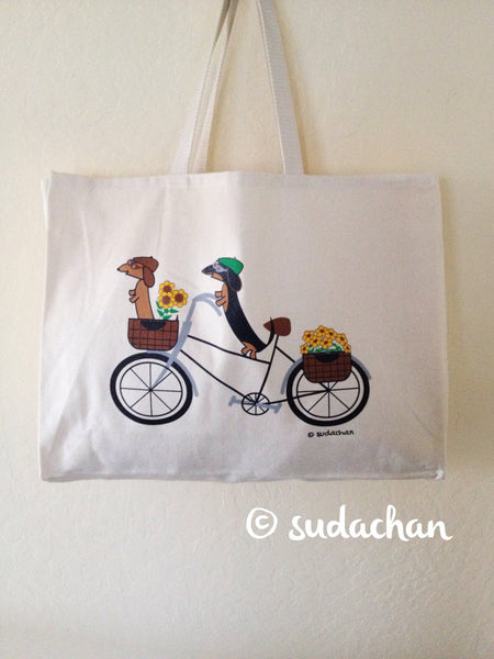 Large  screen printed cotton twill tote bag with two dachshunds wearing riding caps and goggles on a bicycle with baskets of flowers on the bike.