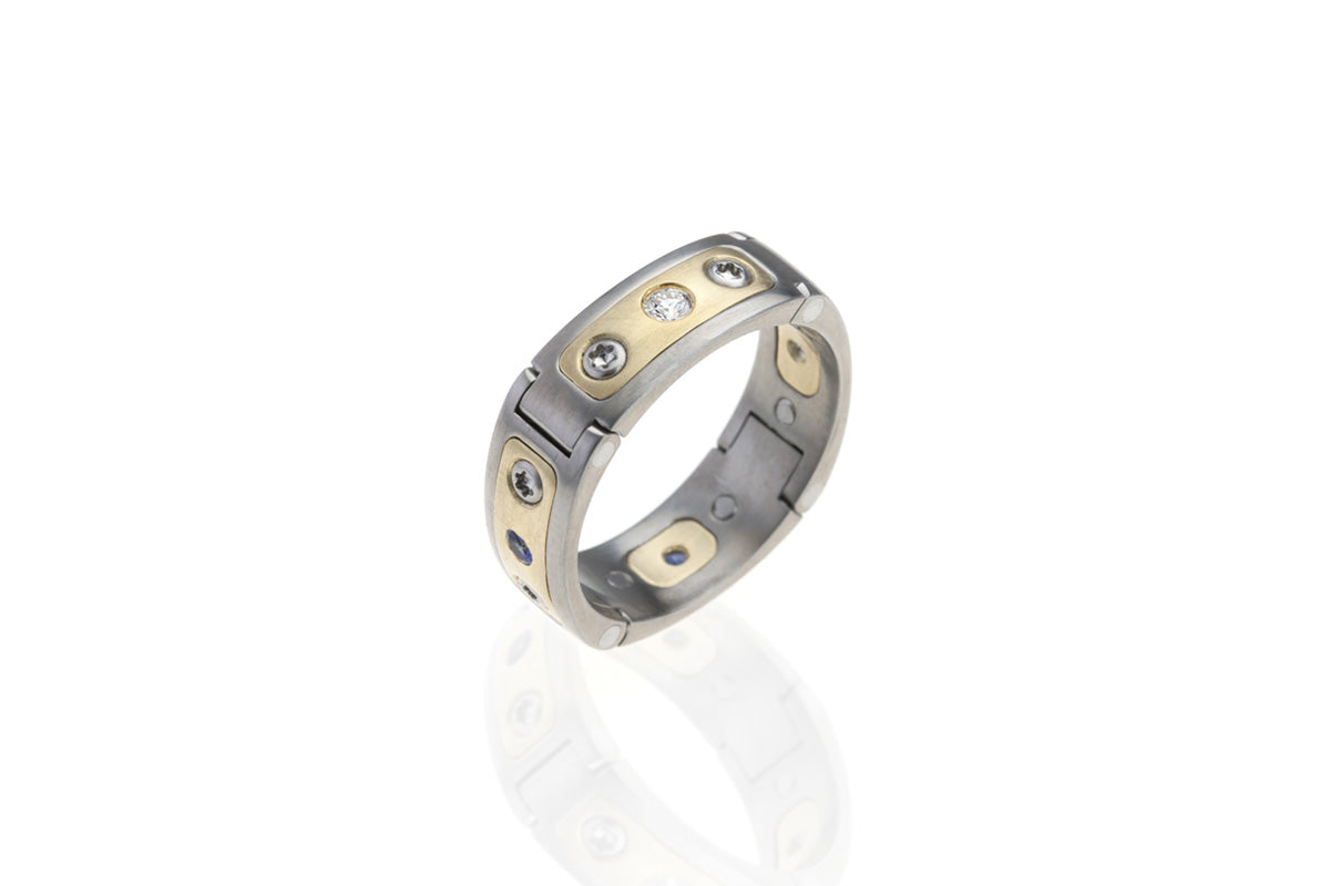 Hinged, Pinch operated, aircraft grade, U.S. made, Titanium, stainless steel, and yellow-gold with diamonds and sapphires openable wedding ring.