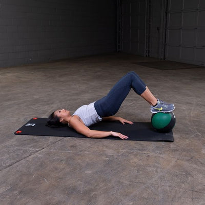 Woman exercising with medicine ball and exercise mat home gym Simpsons Fitness Supply