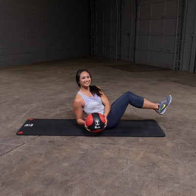 Woman doing sit ups with exercise ball on workout mat medicine ball red and black body solid