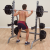 man doing back squats on body solid squat rack