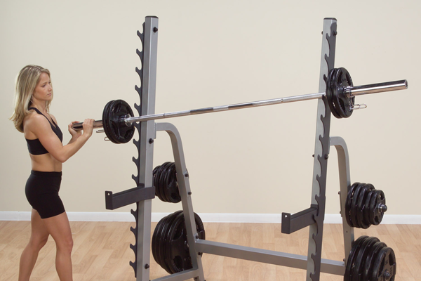 woman racking bar on body solid squat rack