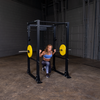 woman doing lunges on body solid power rack barbell and yellow bumper plates