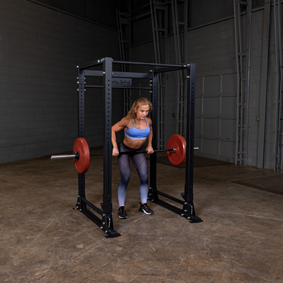 Woman doing standing rows with barbell red bumper plates