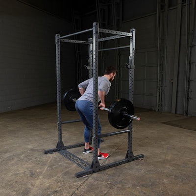 man doing barbell rows on powerline squat rack / cage
