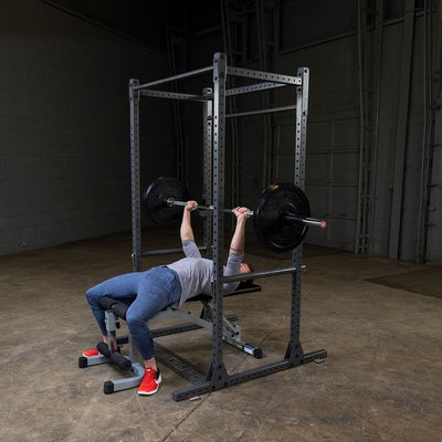 man doing bench press on squat rack by powerline