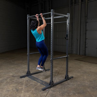 woman doing pull-ups on silver powerline power rack