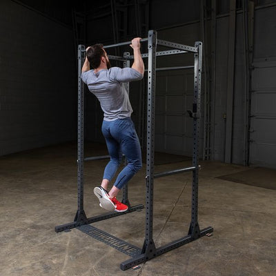 man doing pull-ups on powerline squat rack