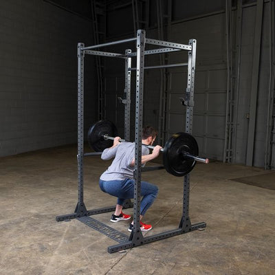 man doing squats on powerline squat rack