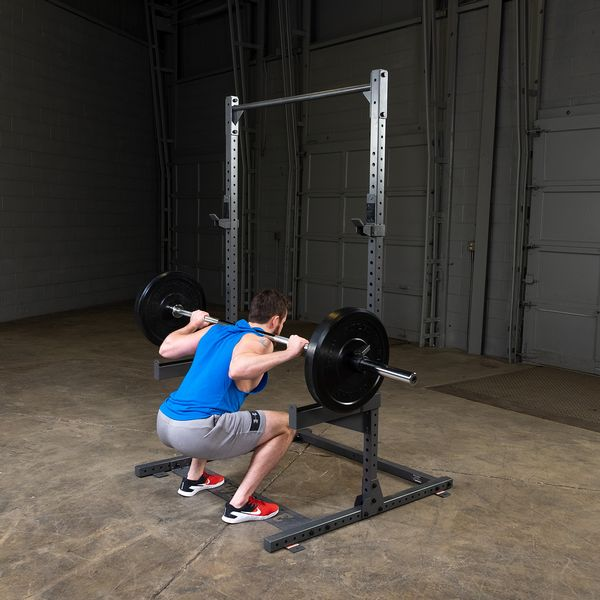 man doing squats on powerline ppr500 half rack with safety spotter arms