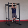guy doing pull-ups on commercial power rack black