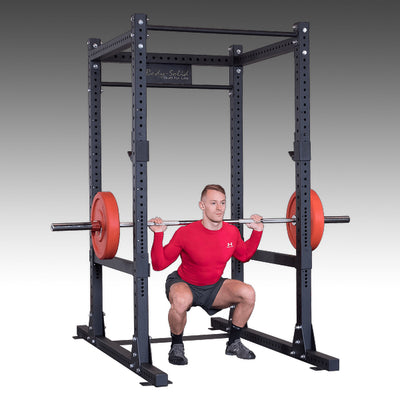 Commercial power rack SPR1000 guy doing back squats with bumper plates