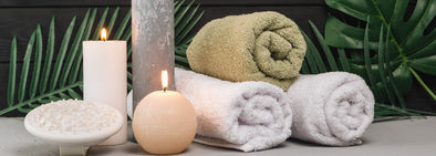 white and green spa towels with candles beside