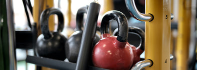 Several kettlebells on metal bar