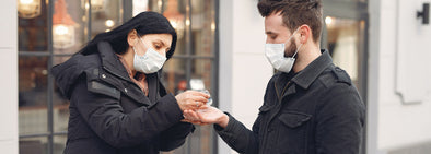 woman putting hand sanitiser on man's hand