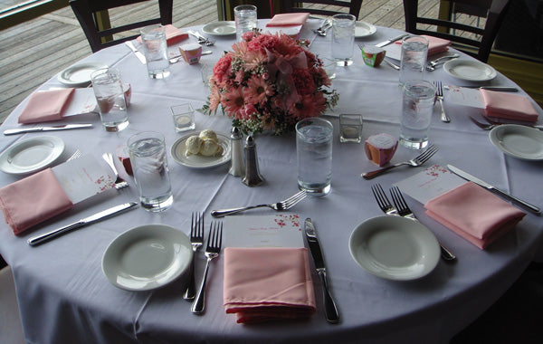 White circle tablecloth  with pink table napkin settings