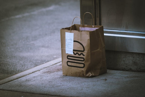 A bag of food delivery at a door unattended