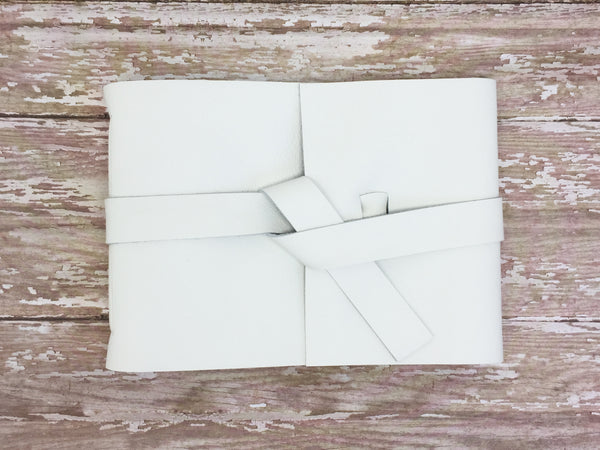 White leather guestbook on wood background